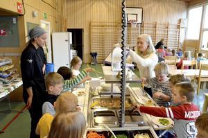 Tillfälllig matsal. Kokt lax och potatis serverades under onsdagen. Eleverna äter på engångstallrikar. Malin Ek, måltidspersonal och Kerstin Löfqvist  Åberg, lärare i klass 1A.