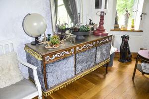 I vardagsrummet har många möbler fått en touch av Ingelas trollspö. Skänken har fått en fuskpälsklädnad och lite tofsar. Till höger syns det lilla bord dom fått en läckert glansig rosa tapet under glasskivan.