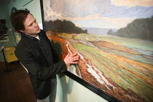Månhusbyggaren Mikael Genberg framför en målning av farfars far jämländske konstnären Anton Genberg på Jamtli.