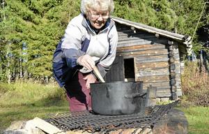 Fixar lunchen. Korvsoppan kokar sakta över elden. Tellervo Niittymäki heter kocken.