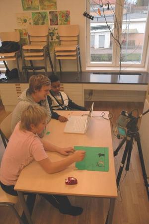 SKAPAR. Framför datorn och ,kameran kommer Samit och Felix på mer detlajer i sitt råndrama. Ledaren Emil Stenberg assisterar.