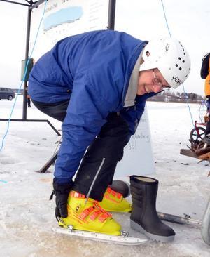 Lennart Fyrk spänner fast sina slalompjäxor på skridskoskenor - han ska ut och åka draksegel på skridskobanan.