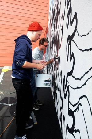 Daniel Götesson och NilsKristofersson målar den nya väggen vid skidstadion i Östersund.