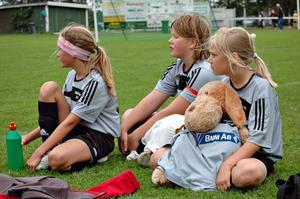 MASKOT. Elin Larsson, Felicia Beijer och Ebba Ekman, Månkarbo-Ullfors, håller i lagets maskot i väntan på spel.