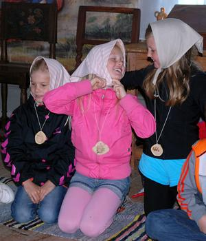 Inför dagen på Skedvi hembygdsgård gjorde barnen en tidsresa, de fick nya tidsenliga namn på en platta runt halsen och flickorna ett huckle och pojkarna en kepa av gammalt snitt.