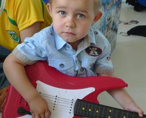 Albin har lånat kusinens gitarr, sitter och funderar lite och snart kommer det nog en rocklåt.