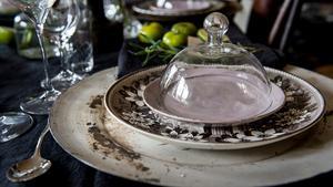 En kupa av glas fredar maten från flugor samtidigt som den är ett dekorativt inslag på bordet.