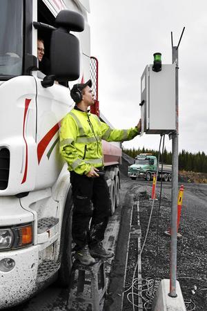 Per Karlsson kontrollerar invägningen av lastbilar till området med chauffören Leif Eliasson, Ottossons åkeri, i bilen. Omkring 100 bilar passerar invägningen i det här skedet av parkbygget.
