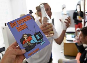 Stina Samson från satirgruppen Riktiga Moderaterna, teatergruppen Nationalscen, bjuder på mousserande vin under en bokrelease av en nyutgåva av Fredrik Reinfeldts bok Det sovande folket från 1993 under Almedalsveckan i Visby.