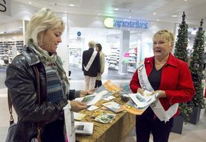 Christine Styrman, ordförande i Hudiksvallsortens Demensförening, delar ut informationsmaterial till Gunilla Bergqvist, som själv jobbar med yngre dementa vid Lyckbacken i Njutånger.