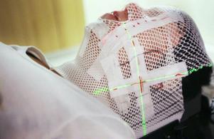 Det gäller att inte ha anlag för klaustrofobi när man ska på med denna mask innan strålning. Maria Hemmingsson måste ligga blick stilla under strålningen