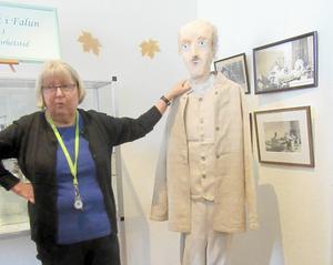 Guiden Kaarina Jansson visar med hjälp av en fullstor docka hur dåtidens patientläder såg ut.