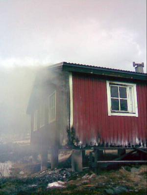 Räddningstjänstens bild av Stensdalsstugan strax före klockan 16. Trots god tillgång till släckningvatten så gick byggnaden inte att rädda.