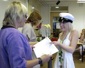Lovisa Åkesson tar emot slutbetyget och en ros av lärarna Britt Nordling och Madeleine Thorley.