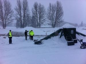 Ett 15-tal personer hjälptes åt att skotta snö från tennistältet.