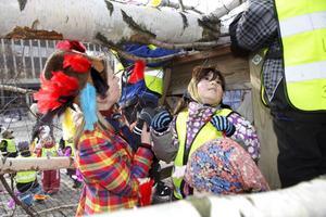 Påskbjörken på plats på Stora torget i Västerås. Nicole Contreras hjälper till med fjädrarna.