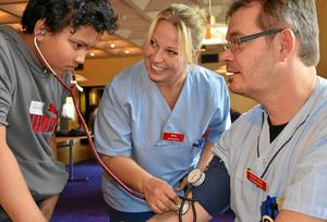 Arbete med stetoskop. Muhamed Husein Hasbullah undersöker Daniel Frisks puls och blodtryck med assistans av Marika Wiker.