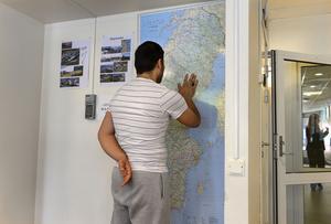 En man tittar på en Sverigekarta i Migrationsverkets anläggning i Märsta.