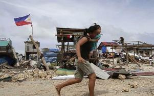 Boende skyndar förbi förstörda hus där återuppbyggnadsarbetet redan påbörjats. Foto: Bullit Marquez