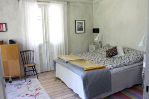 Ljust och ombonat sovrum med putsyta på väggen.