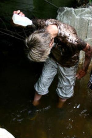 Dennis Bufvers skölja av sig den värsta leran från kläderna i bäcken.