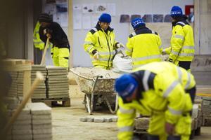 I andra änden av den stora lokalen pågår en utbildning i stenläggning.