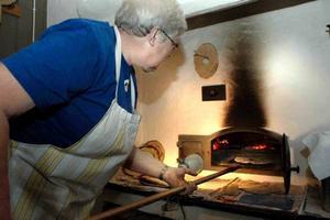 GRÄDDAR. Med hjälp av brödspaden för Britt Rosenberg in ännu en brödkaka i ugnen.