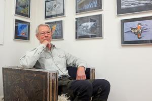 Mats Ricklund framför några av sina verk. Fåtöljen har hans pappa Folke tillverkat med egna målningar. Det är inte den enda målningen av honom i Ricklunds galleri