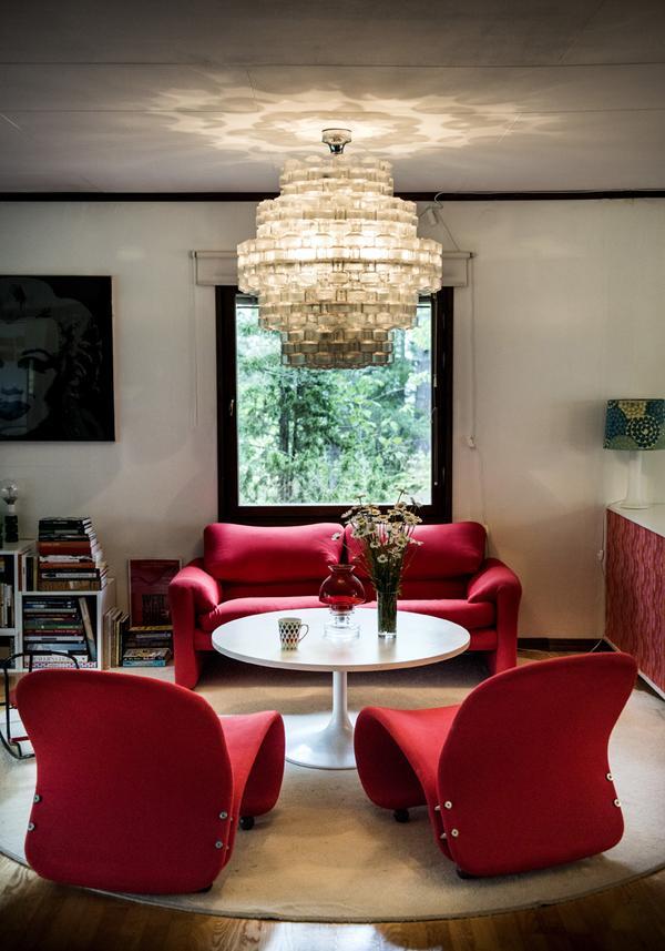 Den röda Maralunga-soffan av Vico Magistretti och Verner Panton-fåtöljerna har fått ny röd klädsel. Taklampan är designad av Gert Nyström.