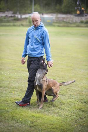 Erik Wiklund övar sin belgiska vallhund Mara att följa honom exakt i varje steg.