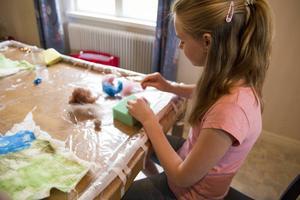 Alva Skyttner använder nål för att forma ullen.