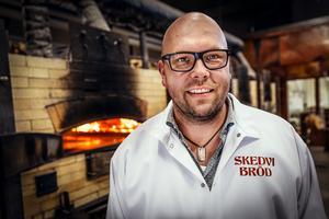 Anders Åkerberg i bageriet med bakugnarna i bakgrunden.