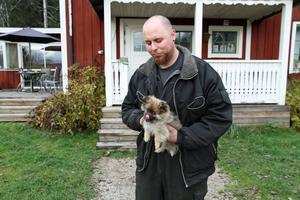 Morgan Plym med hundvalpen Stella utanför hemmet i Ockelbo. Hunden skänktes till familjen efter att en varg dödat familjens hund med samma namn.
