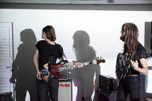 Gudmar Söderin på elbas och Patrick Lantz på elgitarr kastar sina skuggor över väggen där videokonst av Teodor Juel Eckerström spelas upp.
