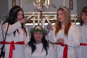 Los lucia, Angeliqa Hellstadius, får ljusen i kronan tända av tärnorna Sandra Broberg, till vänster, och Lovisa Persson, till höger.