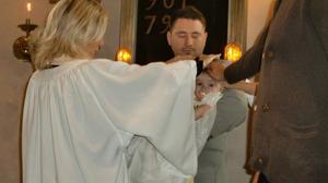 Viggo blir välsignad av präst, föräldrar, storebror och faddrar.