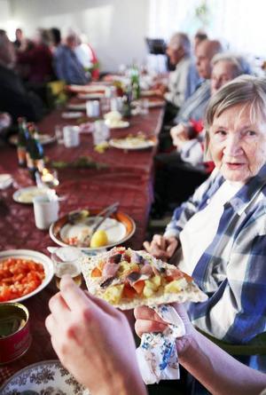 Suring, potatis, tomat och lök på ett hårt tunnbröd. Maj Björk är en av de boende som med glädje deltar i surströmmingsmiddagen.