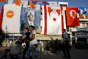Den turkcyptriotiske ledaren Dervis Eroglu, den illegala ockupationsflaggan samt Turkiets flagga. Turkiets ockupation hindrar turkcyprioternas rättheter i EU.