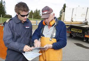 Piloten Jonas Grinde och Tor Eriksson går igenom var fisken ska sättas ut i år.